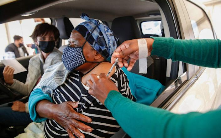 A woman receives a second dose of the Pfizer Covid-19 vaccine from a health worker while her employer looks on at the Zwartkops Raceway in Centurion, South Africa on 13 August 2021 - Phill Magakoe/AFP