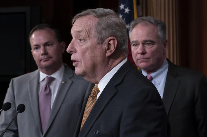 Sen. Dick Durbin, D-Ill., center, flanked by Sen. Mike Lee, R-Utah, left, and Sen. Tim Kaine, D-Va., speaks to reporters just after the Senate advanced a bipartisan resolution asserting that President Donald Trump must seek approval from Congress before engaging in further military action against Iran, at the Capitol in Washington, Wednesday, Feb. 12, 2020. (AP Photo/J. Scott Applewhite)