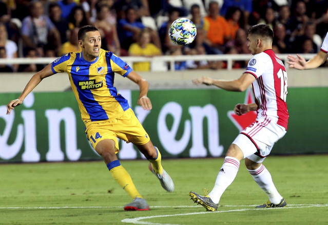 Ajax's Razvan Marin, right, challenges for the ball with APOEL's Uros Matic during the Champions League qualifying play-off first leg soccer match between APOEL Nicosia and AFC Ajax at GSP stadium in Nicosia, Cyprus, Tuesday, Aug. 20, 2019.(AP Photo/Philippos Christou)