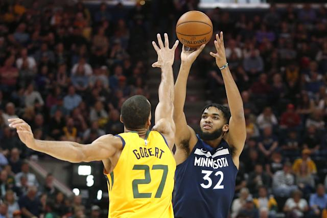 Minnesota Timberwolves center Karl-Anthony Towns (32) shoots as Utah Jazz center Rudy Gobert (27) defends in the first half during an NBA basketball game Monday, Nov. 18, 2019, in Salt Lake City. (AP Photo/Rick Bowmer)