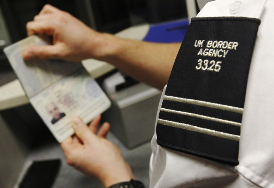 A UK Border Agency worker poses with a passport