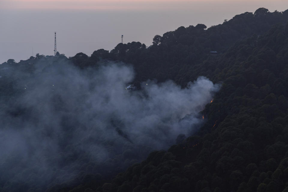 Smoke rises from a fire in a pine forest in Dharmsala, India, Thursday, Oct. 29, 2020. (AP Photo/Ashwini Bhatia)