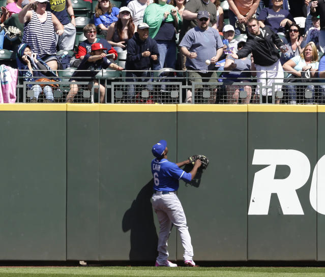 Kansas City Royals center fielder Lorenzo Cain watches as a fan tries to catch a home run hit by Seattle Mariners Dustin Ackley in the fourth inning of a baseball game, Sunday, May 11, 2014 in Seattle. The home run was Ackley's second of the game. (AP Photo/Ted S. Warren)