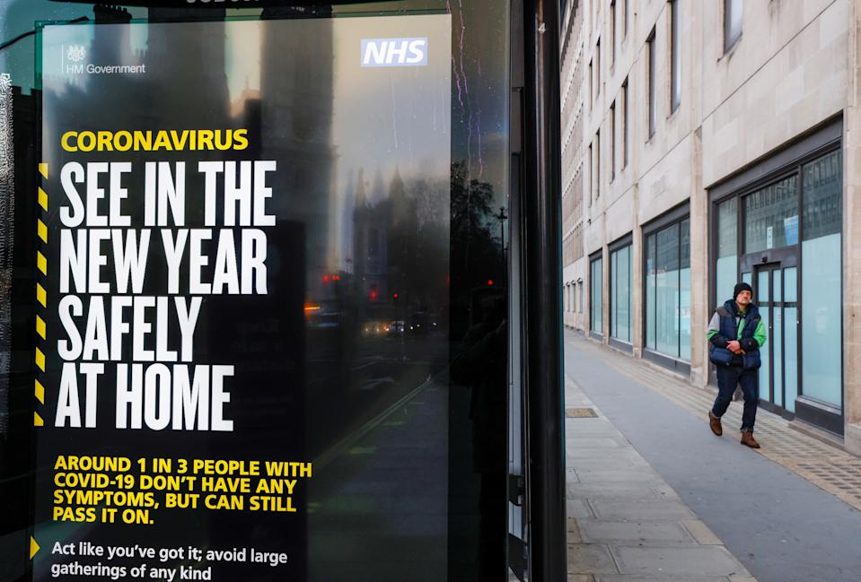 A man walks past a British governments advertisement sign reminding people to stay at home in the New Year, in London, Britain, December 31, 2020. REUTERS/John Sibley
