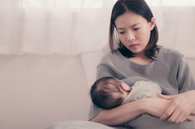 Mother Feeding Baby Boy While Sitting On Bed At Home