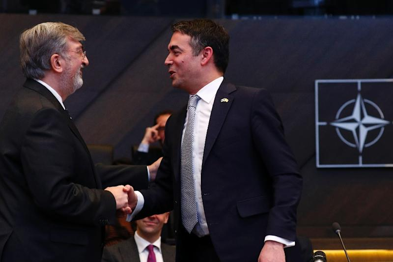 Greek NATO representative Spiros Lambridis (L) shakes hands with Macedonian Foreign Minister Nikola Dimitrov after the signature ceremony of the accession protocol between the Republic of North Macedonia and NATO on February 6, 2019 (AFP Photo/FRANCOIS LENOIR)