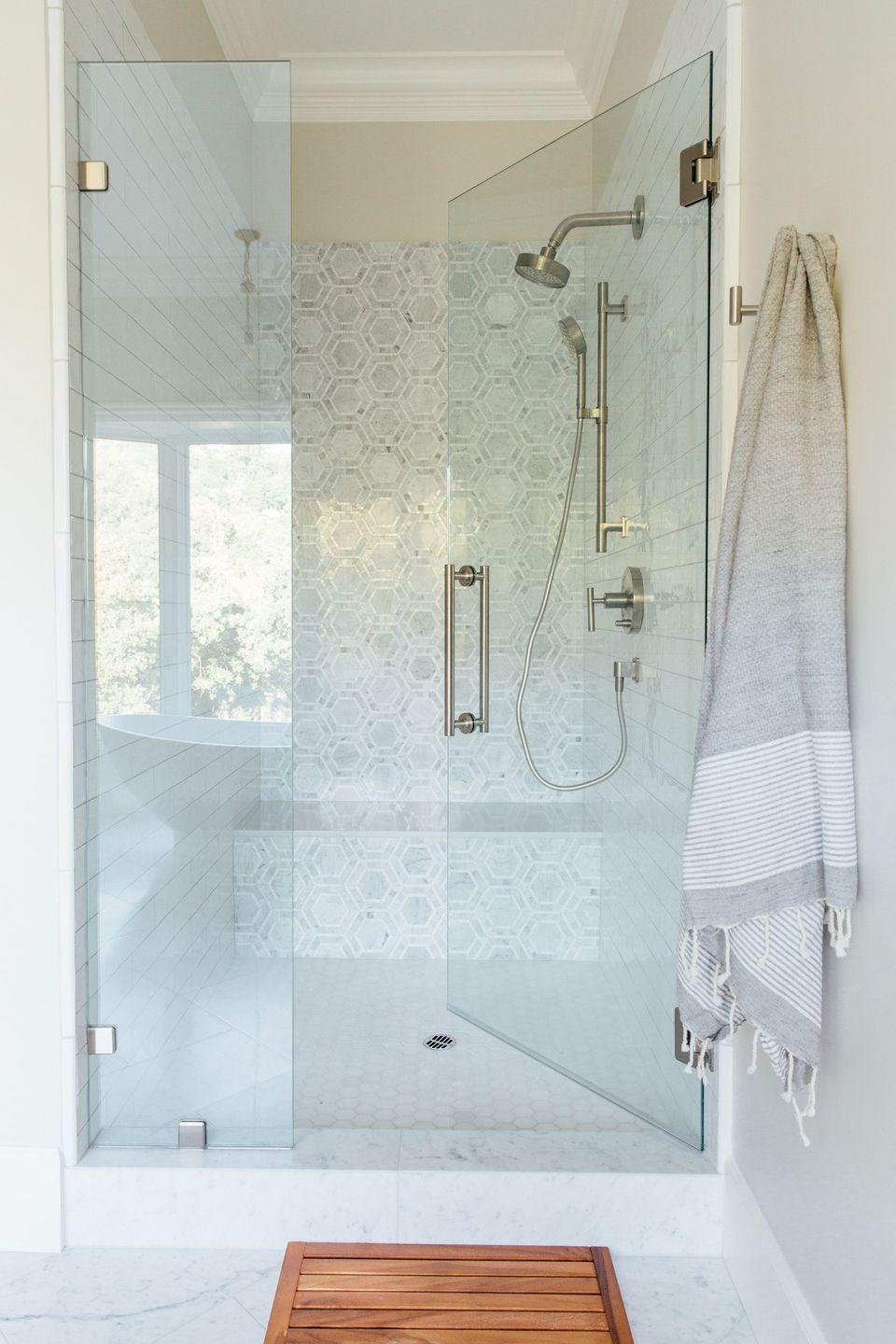<p>Glass doors are the easiest way to get an open look without letting water get all over the place with each shower. The door on this shower by Michelle Lisac Interior Design allows light to come in through the window, which will also make the space feel more open and airy.</p>