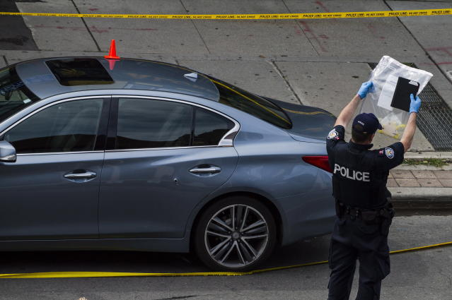 <p>Police are photographed investigating a car with a bullet hole within the scene of a mass shooting in Toronto on July 23, 2018. (Photo: Christopher Katsarov/The Canadian Press via AP) </p>