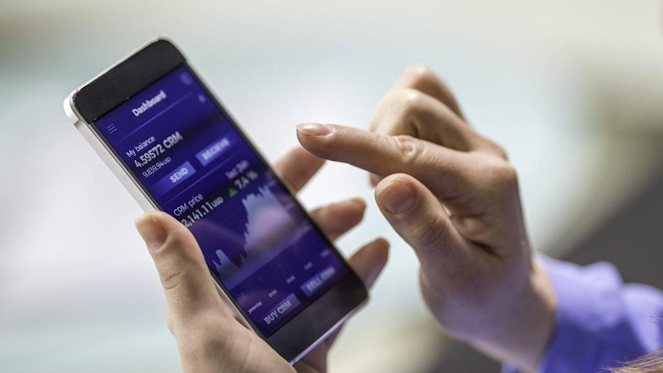Close-up photo of a woman buying cryptocurrency through a smart phone app that is also showing the growth graph.