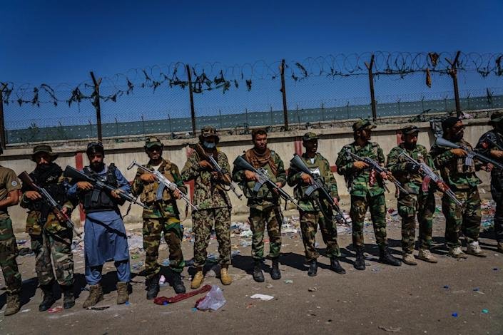 Taliban fighters line up with rifles in front of a fence