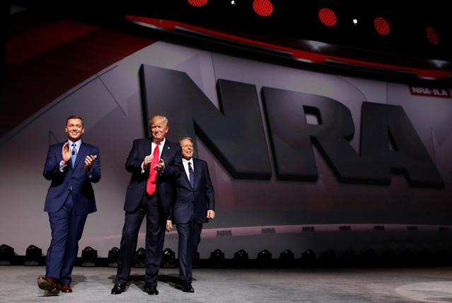 NRA Executive Director Chris Cox, left, and Executive Vice President and CEO Wayne LaPierre, right, welcome President Donald Trump onstage to deliver remarks at the National Rifle Association Leadership Forum in Atlanta on April 28, 2017.