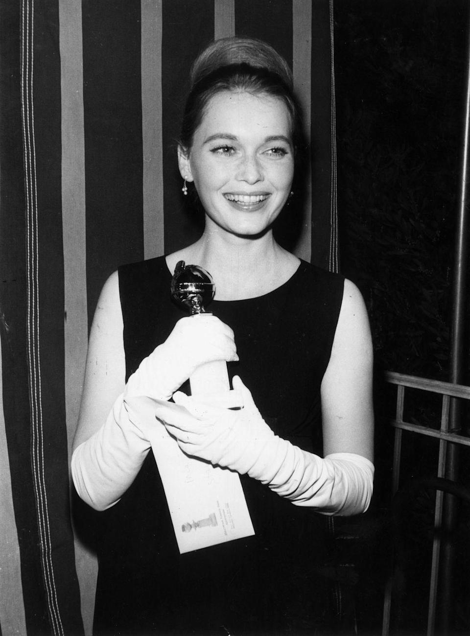 <p>Mia Farrow went for the<em> Breakfast at Tiffany's </em>look with a form-fitting black dress, long white gloves, and a high bun in 1965. </p>