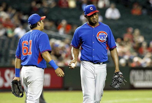 Chicago Cubs' Jose Veras, right, gets the baseball back from teammate Christian Villanueva (61) after the two collided in the infield trying to run down a slow grounder in the ninth inning of a spring training baseball game against the Arizona Diamondbacks, Friday, March 28, 2014, in Phoenix. (AP Photo/Ross D. Franklin)