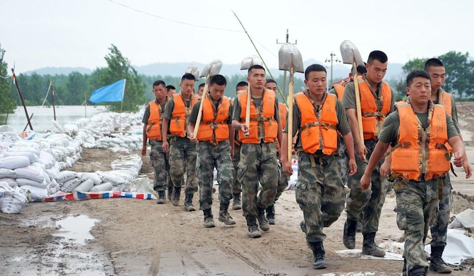 Soldiers help reinforce defences against the rising floodwaters at Jiangzhou. Photo: Tom Wang