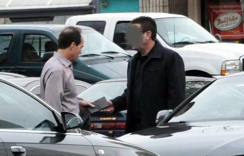 In this undated FBI photo provided by the U.S. attorney's office, KPMG partner Scott London, left, allegedly accepts a $5,000 cash bribe from Bryan Shaw earlier this year. Federal prosecutors have charged London with providing Shaw inside information on two California companies, Herbalife Ltd. and Skechers USA Inc. Shaw's face was obscured by the source of the photo. (AP Photo/U.S Attorney's Office)