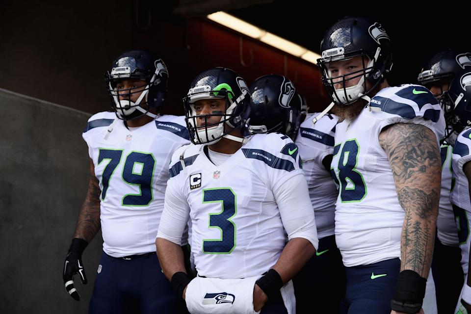 SANTA CLARA, CA - JANUARY 01:  Garry Gilliam #79, Russell Wilson #3, and Justin Britt #68 of the Seattle Seahawks get ready to run on to the field for their game against the San Francisco 49ers at Levi's Stadium on January 1, 2017 in Santa Clara, California.  (Photo by Ezra Shaw/Getty Images)