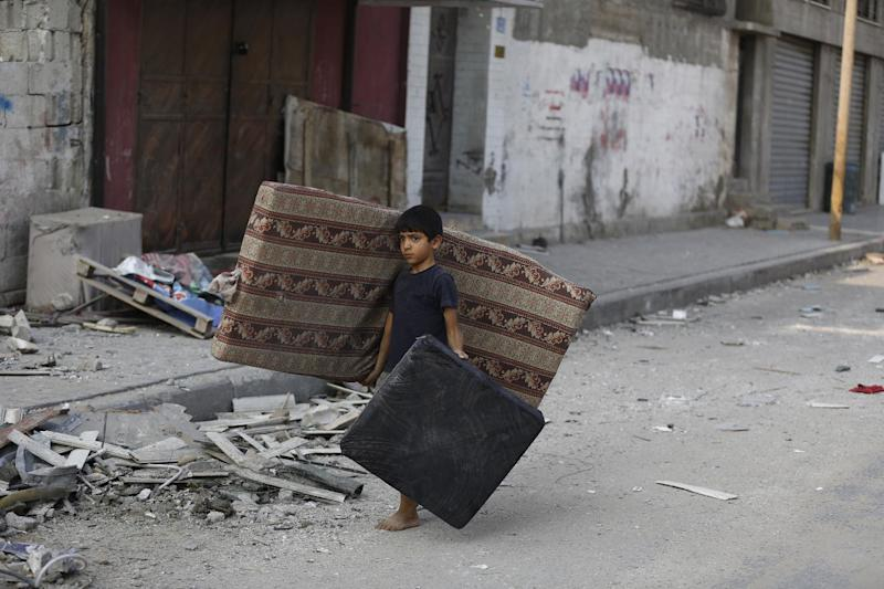 A Palestinian boy carries a mattress he recovered from his family's damaged apartment as he walks amid debris on a deserted street in the centre of Gaza City on July 22, 2014 (AFP Photo/Mohammed Abed)