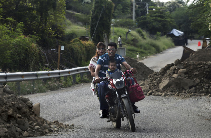 In this Oct. 3, 2019 photo, a family on a motorcycle courses between mounds of dirt and rocks on the outskirts of Tepalcatepec, Michoacan state, Mexico. The region's avocado boom, fueled by soaring U.S. consumption, has drawn parts of western Mexico out of poverty in just 10 years. (AP Photo/Marco Ugarte)