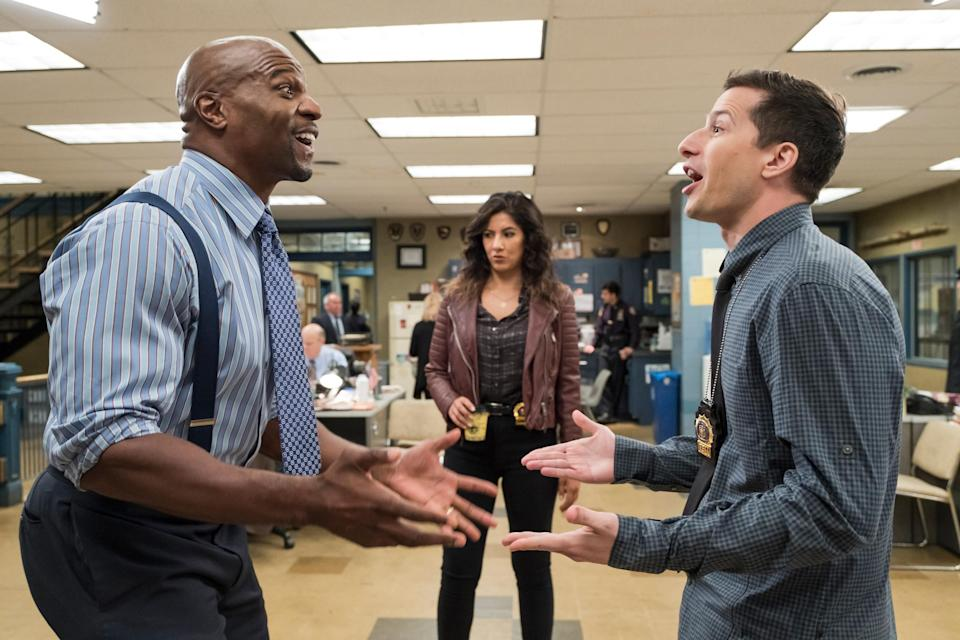 Terry Crews and Andy Samberg argue with Stephanie Beatriz in the background