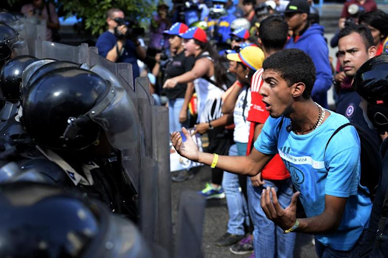 Opponents of Venezuelan President Nicolas Maduro demonstrate in front of riot police in Caracas on January 24, 2015 (AFP Photo/Federico Parra)