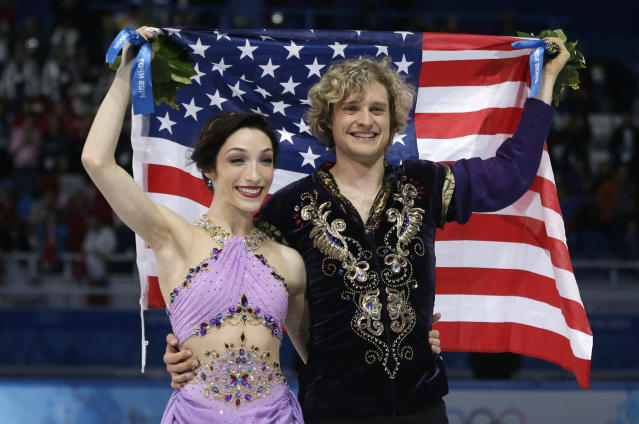 Meryl Davis and Charlie White of the United States pose for photographers with the U.S. flag after placing first in the ice dance free dance figure skating finals at the Iceberg Skating Palace during the 2014 Winter Olympics, Monday, Feb. 17, 2014, in Sochi, Russia. (AP Photo/Darron Cummings)