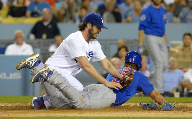 Chicago Cubs' Ryan Sweeney, right, scores on a wild pitch as Los Angeles Dodgers starting pitcher Dan Haren falls over him after missing the throw from A.J. Ellis during the third inning of a baseball game, Friday, Aug. 1, 2014, in Los Angeles. (AP Photo/Mark J. Terrill)