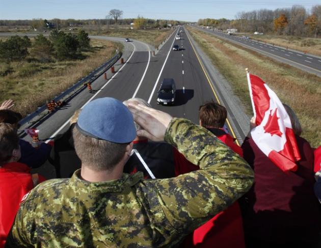A Canadian Soldier salutes the hearse carrying the body of Cpl. Nathan Cirillo.