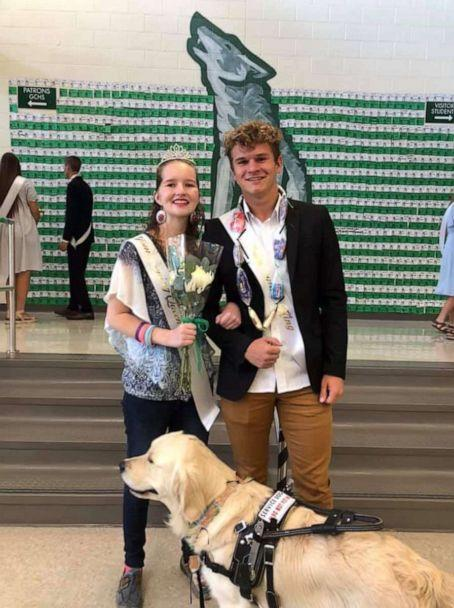 PHOTO: Deserae Turner and the homecoming king pose with her service dog at their school's homecoming assembly. (April Turner)