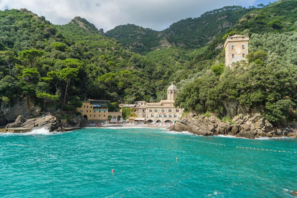 """Located about halfway between Portofino and the small town of Camogli, San Fruttuoso is as idyllic as <a href=""""https://www.cntraveler.com/galleries/2014-08-01/italy-s-most-beautiful-beaches?mbid=synd_yahoo_rss"""" rel=""""nofollow noopener"""" target=""""_blank"""" data-ylk=""""slk:Italian beaches"""" class=""""link rapid-noclick-resp"""">Italian beaches</a> come—and that's saying something. The small cove's appeal lies in its hidden location (you can only reach it by hiking from Portofino or <a href=""""https://www.golfoparadiso.it/"""" rel=""""nofollow noopener"""" target=""""_blank"""" data-ylk=""""slk:catching a ferry"""" class=""""link rapid-noclick-resp"""">catching a ferry</a>), gorgeous blue water, and backdrop of a medieval abbey surrounded by mountains."""