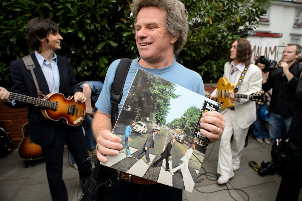 """A man holds a copy of the Beatles album """"Abbey Road"""" as the cast of the musical """"Let It Be"""" preapre to perform near famous Abbey Road zebra crossing in London, England on August 8, 2014, the 45th anniversary of the day that the iconic Beatles album cover photograph was taken.  AFP PHOTO/Leon Neal        (Photo credit should read LEON NEAL/AFP/Getty Images)"""