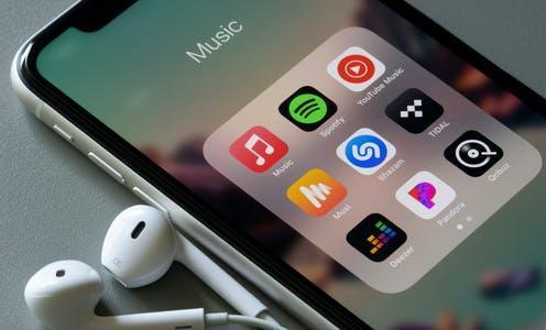 """<span class=""""caption"""">Playlists curated by major music streaming platforms tend to reduce the revenue of smaller artists.</span> <span class=""""attribution""""><a class=""""link rapid-noclick-resp"""" href=""""https://www.shutterstock.com/image-photo/portland-usa-mar-13-2021-assorted-1935354940"""" rel=""""nofollow noopener"""" target=""""_blank"""" data-ylk=""""slk:Tada Images/Shutterstock"""">Tada Images/Shutterstock</a></span>"""