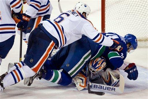 Edmonton Oilers' Ryan Whitney, left, checks Vancouver Canucks' Maxim Lapierre against Edmonton goalie Devan Dubnyk during the second period of an NHL hockey game in Vancouver, British Columbia, on Tuesday, Jan. 24, 2012. (AP Photo/The Canadian Press, Darryl Dyck)