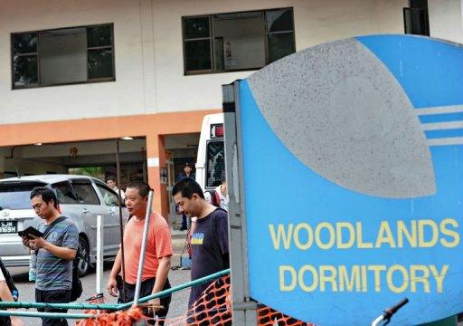 Foreign workers walk out of their dormitory in Singapore