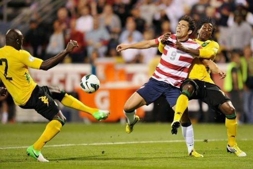 Herculez Gomez (C) of the US team is held back by Jamaica's Rodolph Austin (R), as Nyron Nosworthy takes control of the ball during their World Cup qualifying match on September 11. The US football team got their qualifying campaign back on track with a 1-0 win