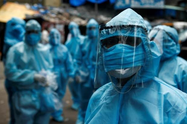 Health care workers wait to take off their personal protective equipment (PPE) after the end of a check-up camp for the coronavirus disease (COVID-19) at a slum in Mumbai, India, on June 14, 2020. (Francis Mascarenhas/Reuters - image credit)