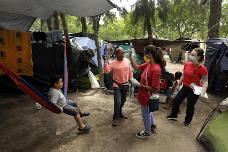"MATAMOROS, MEXICO-MAY 15, 2020-Cuban nurse and asylum seeker Mileydis Tamayo Salgado, 50, second from right, visited tents in the sprawling border camp in Matamoros, Mexico, taking migrants' temperatures with U.S. volunteer Megan Reynolds, 26, right, a registered nurse. They are trying to detect people who have the flu or other coronavirus symptoms. At the Matamoros refugee camp, where hundreds of asylum seekers are waiting under the ""Remain in Mexico"" program, a group of doctors from Cuba, who are also asylum seekers are helping to take care of camp residents at the non-profit Global Response Management clinic. There has yet to be one case of Covid-19 inside the camp during the pandemic, and they are working hard to keep it that way. (Carolyn Cole/Los Angeles Times)"
