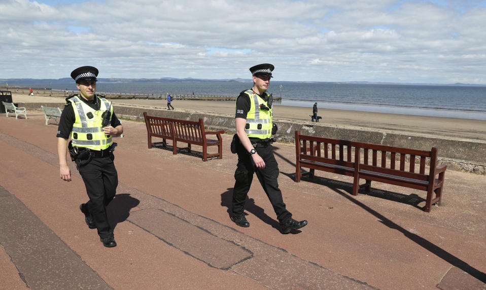 Police officers patrol the beach front at Portobello, in Edinburgh, Scotland,  as the UK continues in lockdown to help curb the spread of the coronavirus, Sunday April 26, 2020. The highly contagious COVID-19 coronavirus has impacted on nations around the globe, many imposing self isolation and exercising social distancing when people move from their homes. (Andrew Milligan / PA via AP)