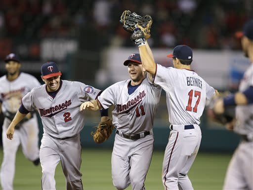 Minnesota Twins' Clete Thomas, center, is congratulated by Doug Bernier, right, and Brian Dozier after catching the ball over the fence during the eighth inning of a baseball game on Monday, July 22, 2013, in Anaheim, Calif. (AP Photo/Jae C. Hong)