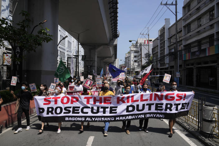 Protesters march during a rally outside the Malacanang palace in Manila, Philippines on Wednesday, June 30, 2021. The group has called for justice and accountability for the thousands who have died due to the government's anti-drug crackdown under the administration of Philippine President Rodrigo Duterte. (AP Photo/Aaron Favila)