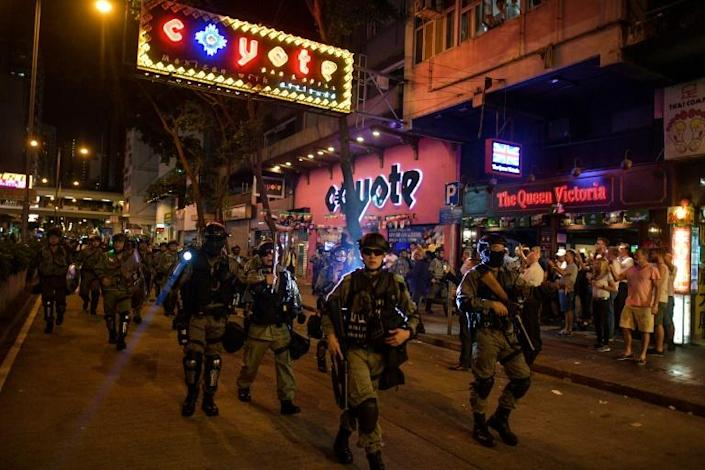 Riot police march past bars in Wan Chai district. The protests were originally triggered by a now-scrapped bill to allow extraditions to mainland China but have morphed into a wider pro-democracy movement (AFP Photo/Nicolas ASFOURI)