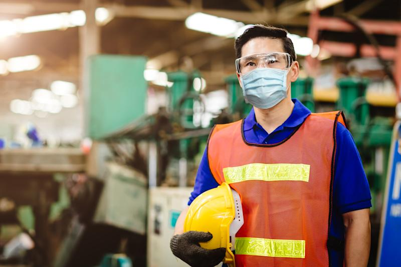 Asian Worker wear disposable face mask for protection coronavirus spreading and smoke dust air pollution filter in factory. Credit: Getty.
