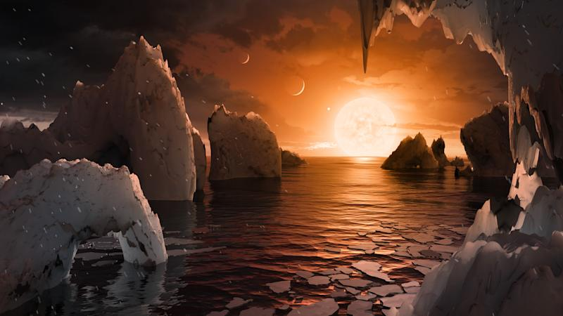 UNSPECIFIED: In this NASA digital illustration handout released on February 22, 2017, an artist's concept allows us to imagine what it would be like to stand on the surface of the exoplanet TRAPPIST-1f, located in the TRAPPIST-1 system in the constellation Aquarius. Because this planet is thought to be tidally locked to its star, meaning the same face of the planet is always pointed at the star, there would be a region called the terminator that perpetually divides day and night. If the night side is icy, the day side might give way to liquid water in the area where sufficient starlight hits the surface. One of the unusual features of TRAPPIST-1 planets is how close they are to each other -- so close that other planets could be visible in the sky from the surface of each one. In this view, the planets in the sky correspond to TRAPPIST1e (top left crescent), d (middle crescent) and c (bright dot to the lower right of the crescents). TRAPPIST-1e would appear about the same size as the moon and TRAPPIST1-c is on the far side of the star. The star itself, an ultra-cool dwarf, would appear about three times larger than our own sun does in Earth's skies. The system has been revealed through observations from NASA's Spitzer Space Telescope as well as other ground-based observatories, and the ground-based TRAPPIST telescope for which it was named after. (Photo digital Illustration by NASA/NASA via Getty Images)