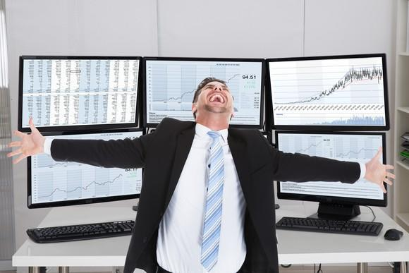 Elated investor in front of numerous computer screens