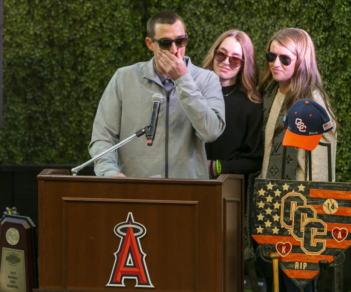 Family members of coach John Altobelli, his son J.J. Altobelli, left, with his fiancee Carly Konigsfeld, right, and his daughter Lexi Altobelli, speaks at a memorial service honoring their father John Altobelli, his wife Keri and their daughter Alyssa who were killed in a helicopter crash on Jan. 26, at Angel Stadium of Anaheim on Monday, Feb. 10, 2020, in Anaheim, Calif. (AP Photo/Damian Dovarganes)
