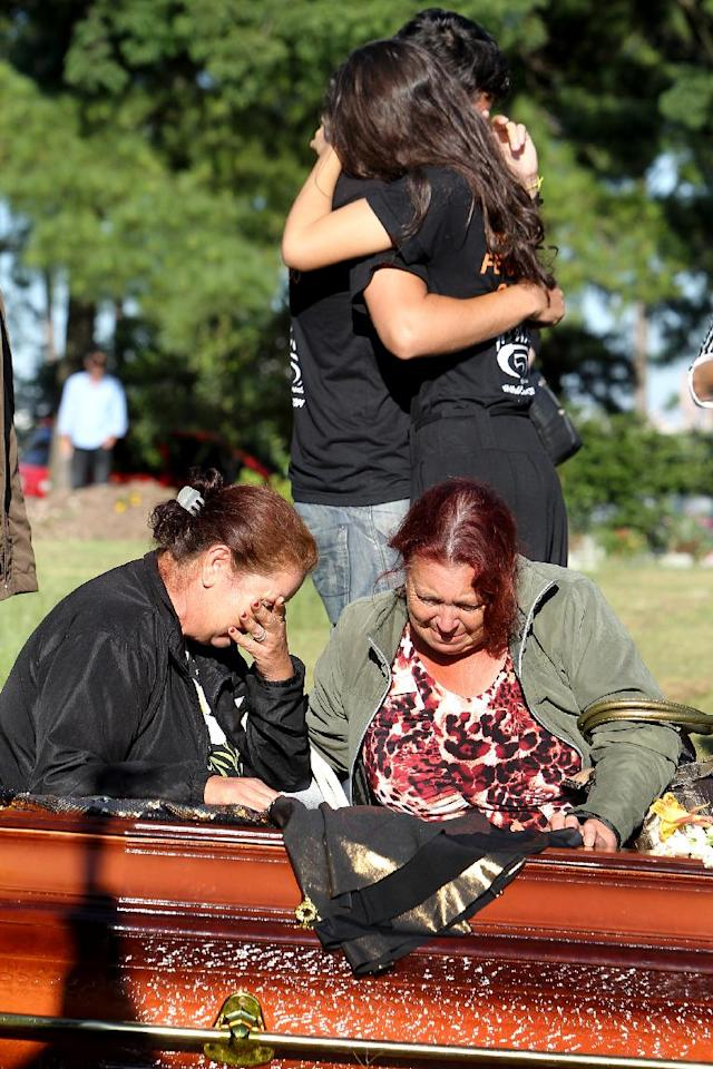 Relatives and friends mourn next to the coffin during the burial of fire victim Tanise Cielo, at a cemetery in Santa Maria city, Rio Grande do Sul state, Brazil, Monday, Jan. 28, 2013. A fast-moving fire roared through the crowded, windowless Kiss nightclub in southern Brazil early Sunday, within seconds filling the space with flames and a thick, toxic smoke that killed more than 230 panicked partygoers who gasped for breath and fought in a stampede to escape. (AP Photo/Nabor Goulart)