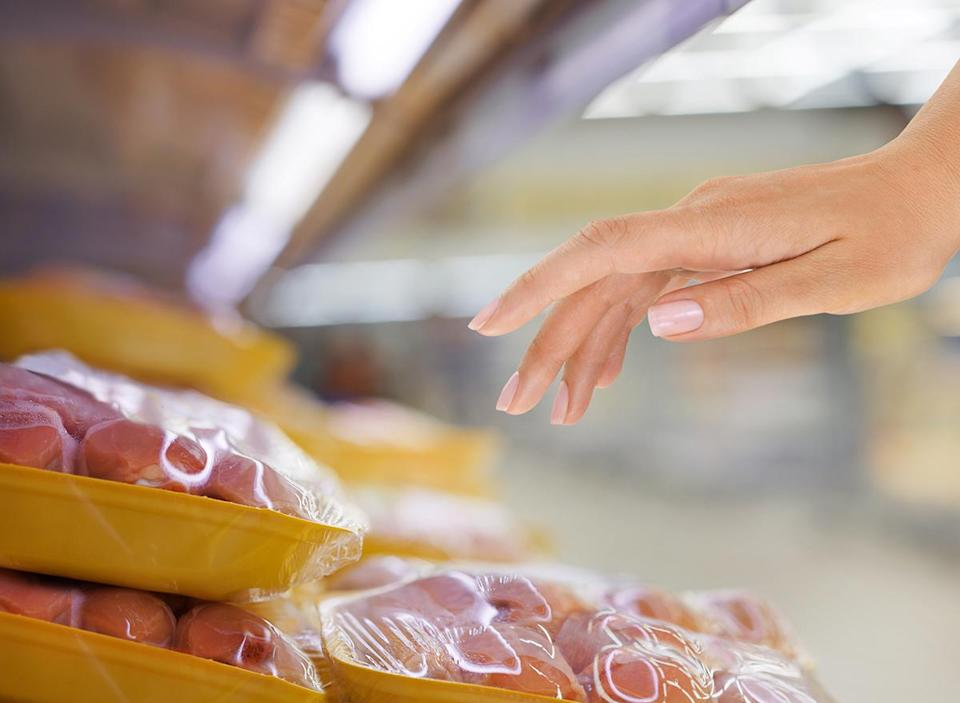 woman reaching for packaged raw chicken in a grocery store