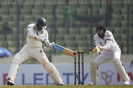 Bangladesh's Shakib Al Hasan (L) plays a shot as Sri Lanka's wicketkeeper Dinesh Chandimal watches during the first day of their first test cricket match of the series in Dhaka January 27, 2014. REUTERS/Andrew Biraj