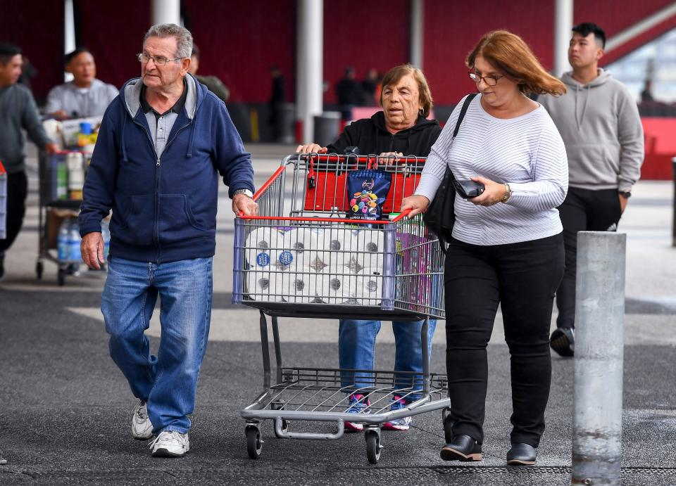 People leave a Costco warehouse with rolls of toilet paper amongst their groceries in Melbourne.