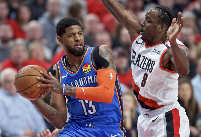 FILE - In this April 16, 2019, file photo, Oklahoma City Thunder forward Paul George, left, looks to pass the ball around Portland Trail Blazers forward Al-Farouq Aminu during the first half of Game 2 of an NBA basketball first-round playoff series in Portland, Ore. A person familiar with the negotiations says the Los Angeles Clippers will be landing Kawhi Leonard as a free agent after they acquire Paul George from the Oklahoma City Thunder in a massive trade for players and draft picks. (AP Photo/Craig Mitchelldyer)