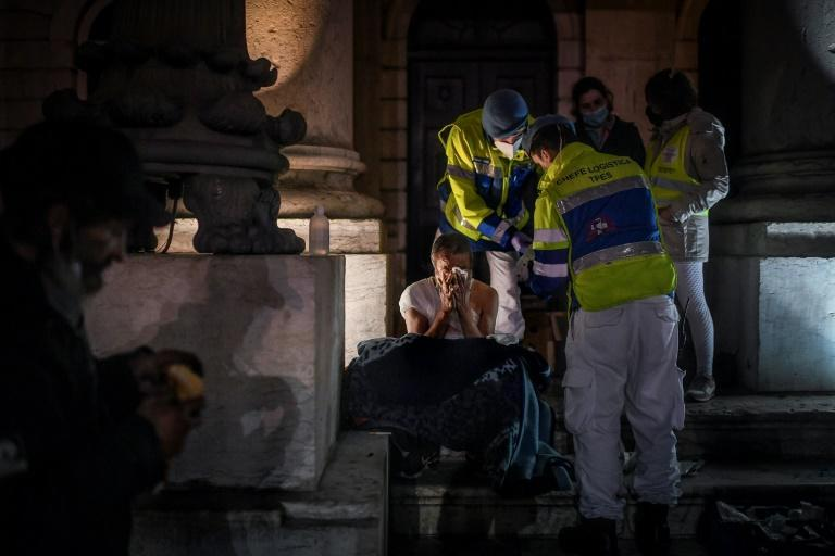 Paramedics give medical assistance to a homeless person in downtown Lisbon